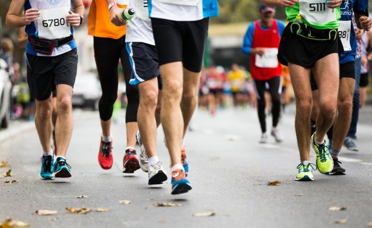 50563123 - marathon running race, people feet on autumn road